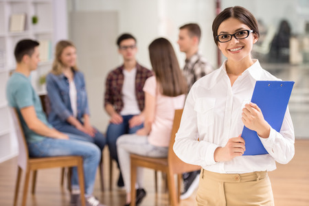 female therapist: Serious female therapist with group therapy in session in background. Stock Photo