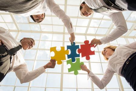 piezas de rompecabezas: Grupo de empresarios montaje rompecabezas y representan el apoyo del equipo y ayuda concepto. Foto de archivo