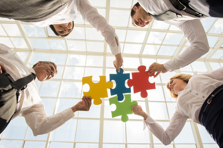 Group of business people assembling jigsaw puzzle and represent team support and help concept.
