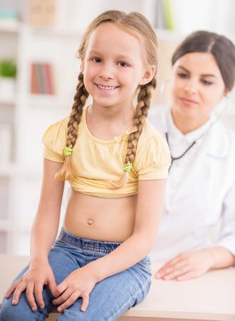 examenes de laboratorio: Doctor atractivo alegre Niña de examen con el estetoscopio.