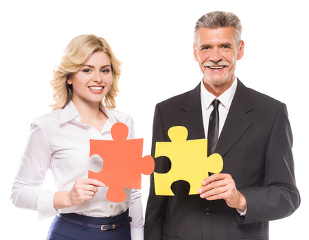 wanting: Confident business people wanting to put two pieces of puzzle together. Business solution concept.