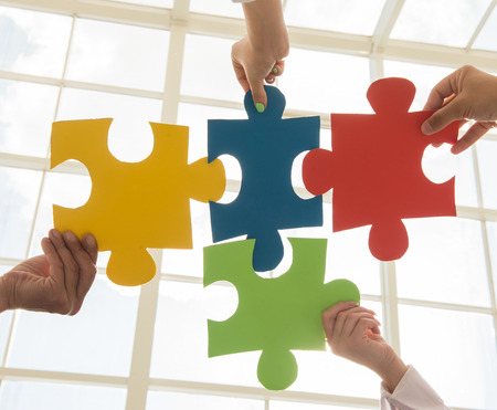 integrate: Group of business people assembling jigsaw puzzle and represent team support and help concept.