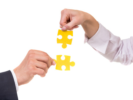 wanting: Close-up of business people wanting to put two pieces of puzzle together.