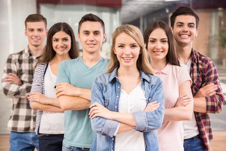 Succesvol team. Groep van vrolijke jonge mensen staan dicht bij elkaar en lachen.
