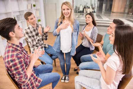 terapia de grupo: Paciente feliz tiene un gran avance en la terapia de grupo, mientras que otros están aplaudiendo ella.