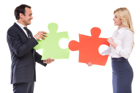 wanting: Successful business people wanting to put two big pieces of puzzle together. White background. Stock Photo