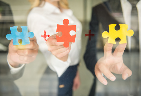 Image of confident business people wanting to put pieces of puzzle together. Close-up. Standard-Bild