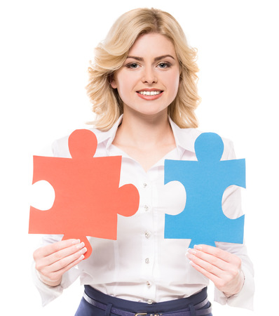 connective: Young beautiful woman in suit trying to connect pieces of puzzle and smiling to camera. Stock Photo
