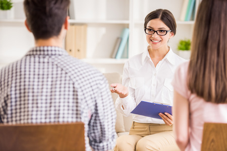 a marriage meeting: Psychologist helping to young couple in her private consulting room. Stock Photo