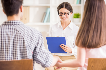 couples therapy: Psychologist helping to young couple in her private consulting room. Stock Photo