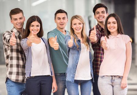 Doe mee met succesvol team! Groep gelukkige jonge mensen staan en tonen duimen omhoog.