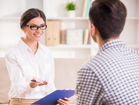 Mann mit einem Gespräch mit seiner Psychotherapeutin auf der Couch im Büro.