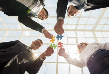 building backgrounds: Image of confident business people wanting to put pieces of puzzle together. Team work. Stock Photo