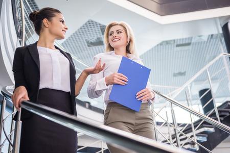 bajando escaleras: Dos mujeres atractivas del bussiness en movimiento por las escaleras y hablando.