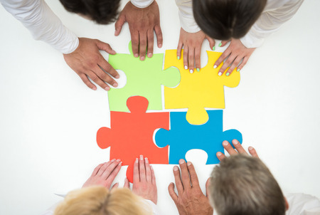 business support: Group of business people assembling jigsaw puzzle and represent team support and help concept. Close-up.