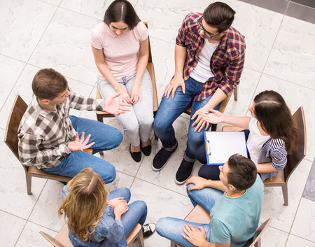 round chairs: Group therapy. Group of people sitting close to each other and communicating.