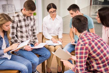Therapeuten im Gespräch mit einem Reha-Gruppe bei Therapiesitzung.