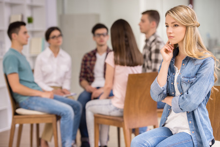 health woman: Young woman at therapy session with rehab group on background. Stock Photo