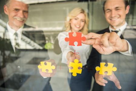 wanting: Image of confident business people wanting to put pieces of puzzle together. Team work. Stock Photo