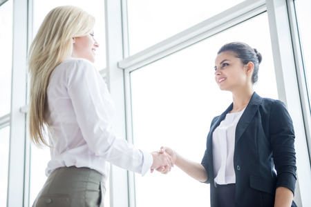 Two young beautiful business women dressed formal shaking hands at office.