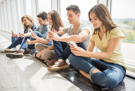 College friends sitting on the floorin line and watching pics on their gadgets at break. Side view. Stock Photo