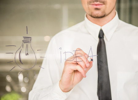 business idea: Young business man drawing an idea on glass window at office. Close-up. Stock Photo