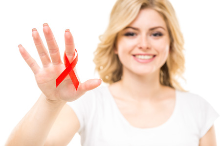 Portrait of young woman holding red AIDS ribbon on white background. Stock Photo