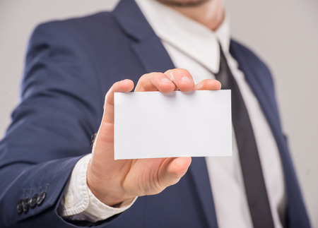 Business man handing a blank business card over gray background. Stock Photo