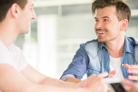 out of business: Two confident colleagues sitting at office and talking out business project. Stock Photo