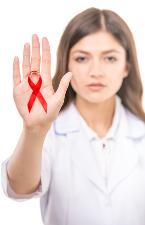 aids symbol: Beautiful female doctor holding red ribbon as a symbol of AIDS.
