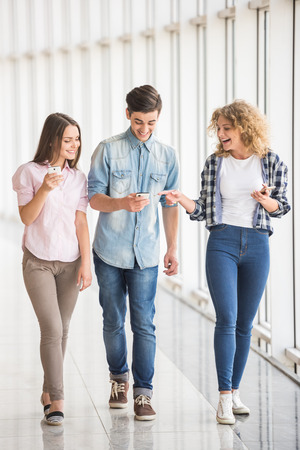 students talking: Group of young positive friends using their phones. Education concept. Full length.