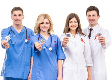 Doctors with red ribbon supporting AIDS awareness campaign, holding condoms in hands. Foto de archivo