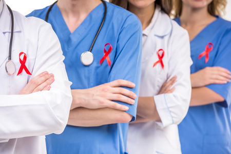 red ribbon: Group of medical doctors with red ribbon for AIDS awareness. White background. Close-up.