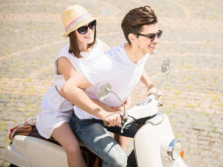 nifty: Young nifty couple riding scooter together, woman hugging his man. Stock Photo