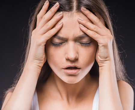 black eye: Young woman feeling headacke and keeping hands on her head over dark background. Stock Photo