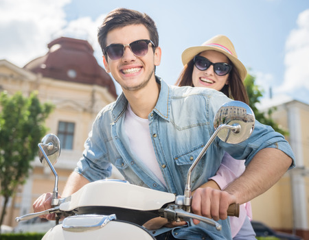 free riding: Beautiful happy couple riding scooter on sunny day. Young and free. Stock Photo