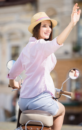 nifty: Beautiful young woman in nifty hat sitting on scooter and smiling. Stock Photo