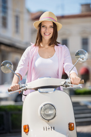 nifty: Young and beautiful woman in nifty hat riding scooter. Stock Photo