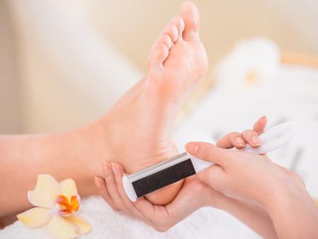 Peeling feet pedicure procedure in a beauty salon.