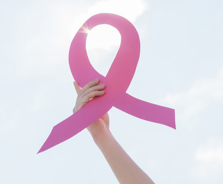 brasiere: Cuidado de la salud y la medicina concepto - mano de la mujer que sostiene la cinta rosada de la conciencia del c�ncer de mama, el cielo de fondo.