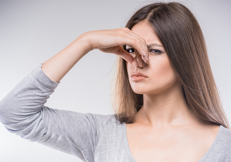 stinks: Beautiful young lady covers nose with hand showing that something stinks. Stock Photo