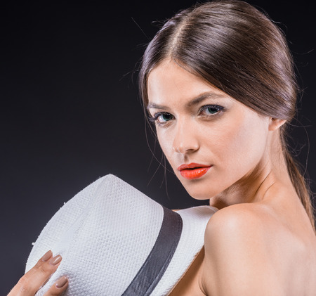 nifty: Feeling flirty. Young beautiful woman holding nifty hat and looking at camera over black background.