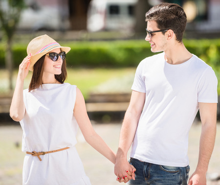 nifty: Young nifty couple walking along the street and looking to each other on sunny day. Front view. Stock Photo