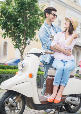 nifty: Nifty young couple talking to each other and smiling while woman sitting on scooter. Weekend together.