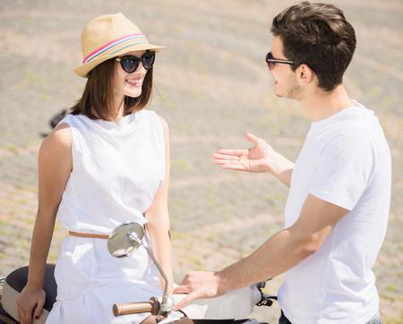 dos personas conversando: Pareja joven Nifty hablar el uno al otro y sonriendo mientras que la mujer se sienta en scooter. Fin de semana juntos.