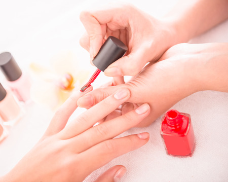 red nail colour: Manicure in the beauty salon. Drawing of red nail polish. Spa treatment.