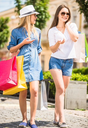 lifestyle shopping: Two young women with shopping bags walking along the street. Side view.