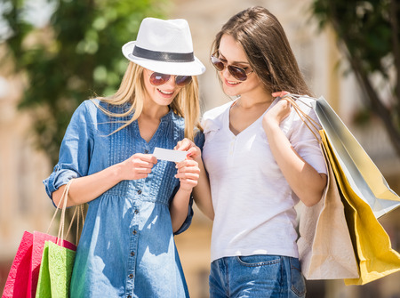 woman holding card: Two beautiful women looking at credit card in the city.