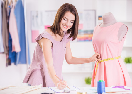 Vrouwelijke mode-ontwerper die meting en het schrijven van het naar beneden.