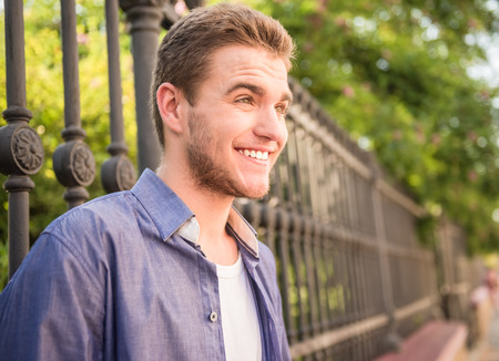 guy standing: Portrait of happy guy standing near the fence in park and looking away. Side view. Stock Photo